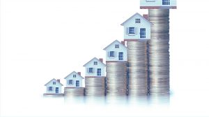 Stacks of money with houses on top