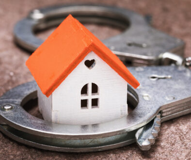 Small toy house and handcuffs. Real Estate Fraud Concept