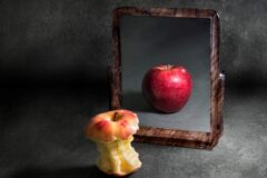 apple with anorexia looking at its reflection in a mirror