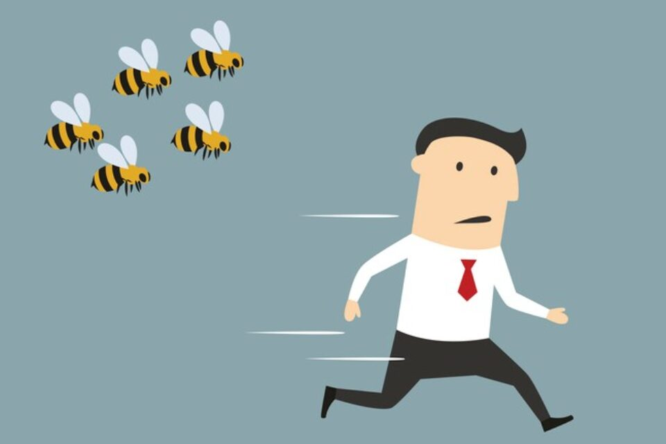 Businessman running away from angry bees