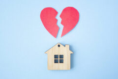 Divorce, division of property, poverty and no money concept. Wooden house with broken heart on bright blue background. Mortgage, rent, realtor