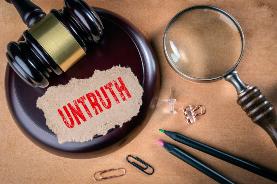 UNTRUTH. Law, regulations and judgment concept. Judge's hammer, stationery and magnifying glass