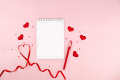 Notebook with red heart shape decorations and red ribbon on pink background. Wedding, Romantic and Happy Valentine day holiday concept.