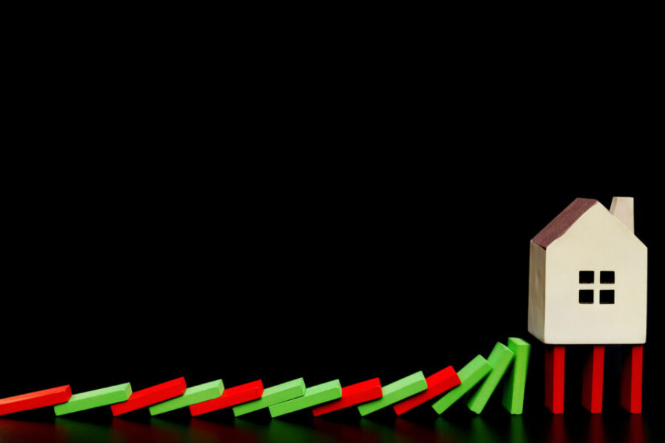 house standing on falling dominos on black background as a financial concept